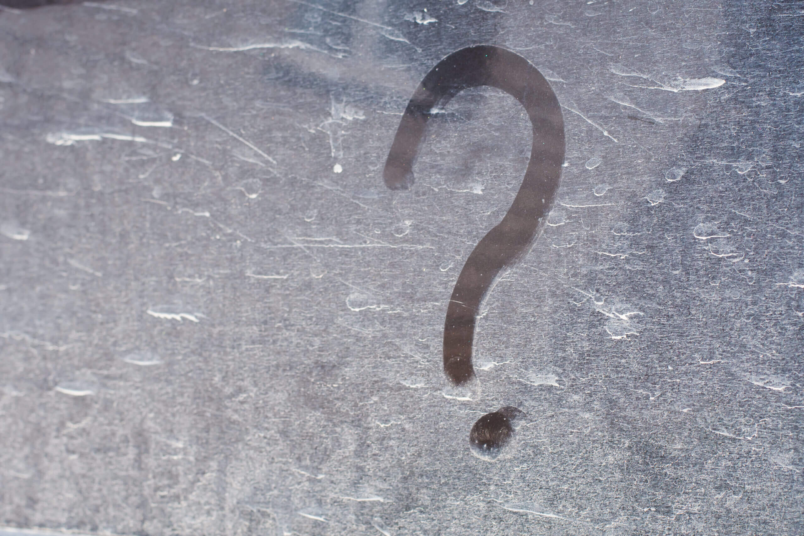 Question mark drawn on dusty surface